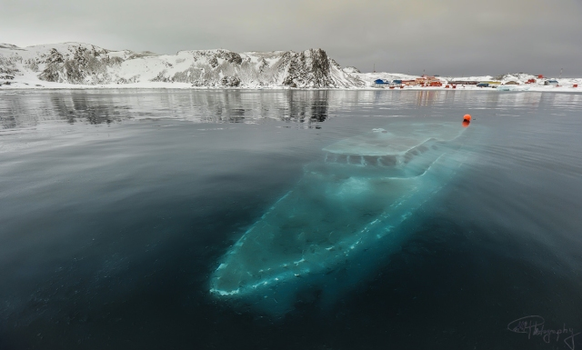 A boat trapped under frozen water, Antarctica
